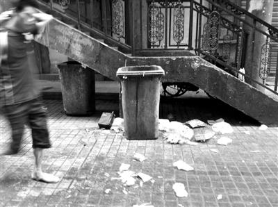 世纪广场小区,垃圾被丢到垃圾桶外,没有扫干净